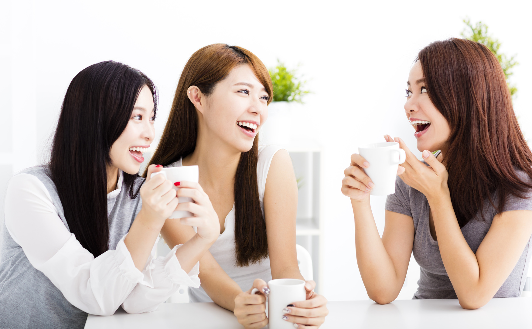 three happy young woman chatting in living room